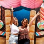 Happy Young Ladies in Front of the Eddie World Artwork